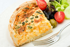 Quiche with salad. A delicious quiche with cheese and leeks on a white plate and a salad of  mixed lettuce, tomatoes, olives and cucumber Royalty Free Stock Image