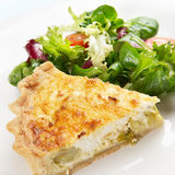 Quiche and salad. A slice of leek and goats cheese quiche on a plate with crispy leaf salad Stock Photo