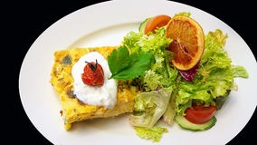Quiche and salad topped by an orange slice, white saucer isolate Stock Image