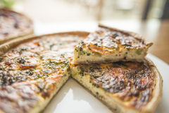 Quiche. A Quiche with a slice taken out Stock Images