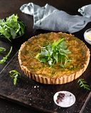 Quiche with spinach,arugula and cheese feta, gruyere on dark background with copyspace. Homemade, traditional french quiche pie royalty free stock photography