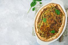 Quiche with spinach and cheese - savory tart from flaky dough on. A white stone backround with copy space Royalty Free Stock Image