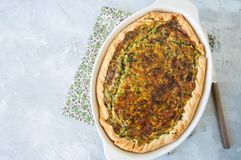 Quiche with spinach and cheese - savory tart from flaky dough on. A white stone backround with copy space Stock Images