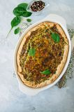 Quiche with spinach and cheese - savoty tart from flaky dough on. A white stone backround with copy space Stock Images