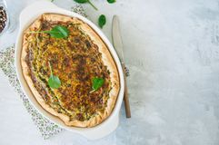 Quiche with spinach and cheese - savoty tart from flaky dough on. A white stone backround with copy space Royalty Free Stock Images