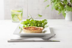 A quiche on a white plate with garnish. An individual mini quiche on a white rectangular plate with green salad garnish a glass of lemon water and cutlery stock image