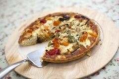 Quiche. A quiche on a wooden plate on a floral tablecloth with a piece missing and a stainless steel slice royalty free stock image