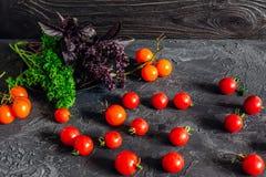 Quiches rouges de cerise avec le persil vert sur la table photographie stock