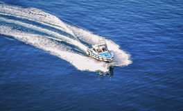 Quick boat on blue sea. Moment when the boat cut through the blue surface at a speed barrier-free, free, on their way Royalty Free Stock Images