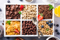 Quick breakfast cereals. Variety of cold quick breakfast cereals with berries in white wooden box, healthy eating for kids, overhead shot royalty free stock images