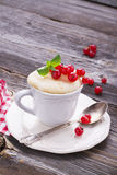 Quick breakfast snack in the microwave for a couple of minutes. Mug  semolina cake with red currants on  wooden Royalty Free Stock Photo