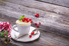 Quick breakfast snack in the microwave for a couple of minutes. Mug  semolina cake with red currants on  wooden Royalty Free Stock Image