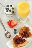 Quick Breakfast - vertical. Quick breakfast consisting of orange juice, strawberroes. toast/jam, and blueberries w/yogurt Stock Images
