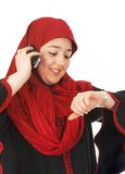 Quick call. Young veiled woman looking at her watch while making a phone call Royalty Free Stock Photos