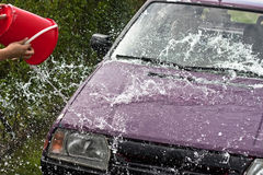 Quick car wash. Pouring and spraying water from backet Royalty Free Stock Photo