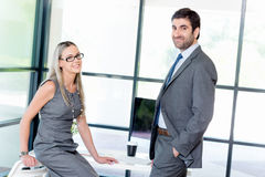 Quick catch up between colleagues. Shot of two collegues having a friendly conversation at the desk Stock Images