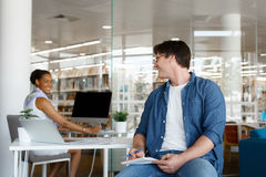 Quick catch up between colleagues. Shot of two collegues having a friendly conversation at the desk Royalty Free Stock Images