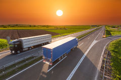 Quick delivery trucks on the empty highway at sunset. Two new trucks for different purposes driving towards the sun. Fast blurred motion drive on the freeway at Stock Images