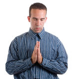 Quick Prayer. A young man wearing a blue striped shirt is giving a quick prayer for something, isolated against a white background Royalty Free Stock Image