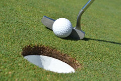 Quick Putt. Golf ball and putter on green Royalty Free Stock Image