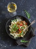 Quick ratatouille pasta and a glass of white wine on dark background, top view. Stock Images
