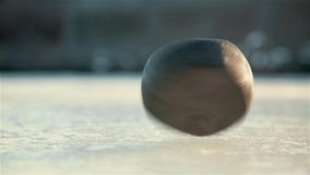 Quick spin of black hockey puck on ice rink HD 1020x1080 stock video footage