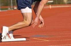 Quick start. Track runner pushing off starting blocks at start of the race Royalty Free Stock Photos