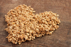 Quick and tasty breakfast granola in a heart shape. On wooden board royalty free stock image