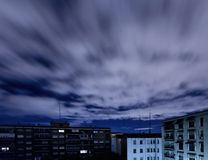Quickening sky over city buildings Stock Photo