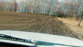 Quickly ride an off-road vehicle on a freshly plowed field, view through the windshield. Agricultural land, POV video. Quickly ride an off-road vehicle on a stock footage