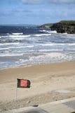 Quicksilver flag flying beside ballybunion beach Royalty Free Stock Photos