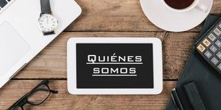 Quienes somos, spansk text för omkring oss på skärmen av minnestavlacom arkivfoto