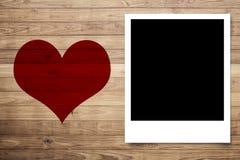 Quiera el corazón y el marco de la foto en la pared de madera del tablón de Brown Fotos de archivo libres de regalías