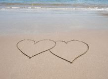 Quiera los símbolos del corazón en arena en la playa tropical Foto de archivo