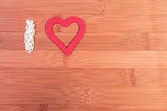 Quiero? a la muchacha triguena joven hermosa que lleva a cabo el corazón rojo grande, aislado en el fondo blanco Foto de archivo libre de regalías