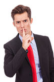 Quiet!. Business man with finger on his lips making the quiet gesture Stock Photo