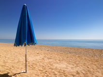 Quiet beach. High rezz beach image.   Deep blue sky, golden sand.  Focus on parasol Royalty Free Stock Image