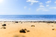 Quiet Beach. Waves and blue waters. Beach with black stones and the sun Royalty Free Stock Photos
