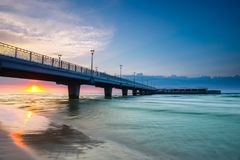 Quiet beach with pier at sunset. Long time exposure stock photo