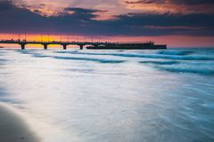 Quiet beach with pier at sunset. Long time exposure stock images