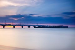 Quiet beach with pier at sunset. Long time exposure royalty free stock images