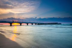 Quiet beach with pier at sunset. Long time exposure royalty free stock photo