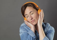 Quiet beautiful middle aged woman listening to relaxing music. On headphones, enjoying relaxation and wellbeing, grey background Royalty Free Stock Photography