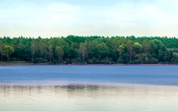 Quiet blue lake with slightly curled surface in front of a forest with dense tree population in front of a cloudy sky. Germany royalty free stock images