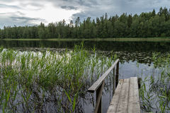 Quiet and calm lake and a wooden pier in Finland. Early evening at a quiet and calm lake, simple wooden pier and reflection of a forest in Finland in summertime stock photo