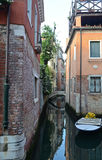 A quiet canal, Venice. A deserted backwater in Venice, with boats and old buildings. The buildings of brick and terracotta are reflected in the water royalty free stock photos