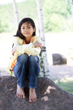 Quiet child sitting under trees. Quiet child sitting on rock under trees Stock Images