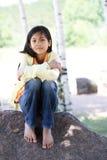 Quiet child sitting under trees Stock Images