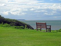 Quiet contemplation beach bench. Photo of a wooden bench ready for quiet contemplation with views across the thames estuary in whitstable kent with isle of Stock Photo