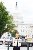 Quiet, corrupt politician in washington dc, holding dollar bills isolated on Capitol building Royalty Free Stock Photo